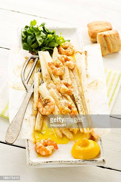 King prawns with white asparagus and basil on plate, close up