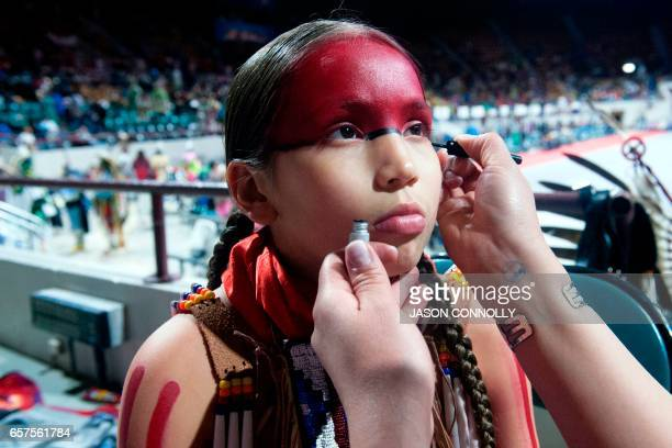 King Ramos of the Oglala Lakota Nation is readied for competition by his mother Mercy prior to the Grand Entry of the Denver March Powwow on March 24...