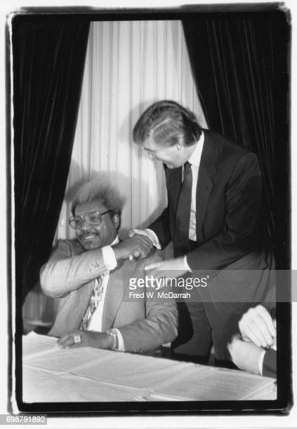 American boxing promoter Don King shakes hands over his shoulder with real estate developer Donald Trump at a press conference New York New York...