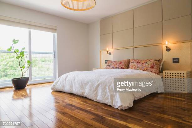 King size bed in bedroom with American walnut hardwood flooring on the upstairs floor inside a modern cube style home, Quebec, Canada