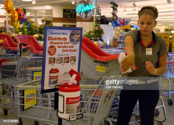DENVER CO SEPTEMBER 7 2005 King Soopers courtesy clerk Dora Moncayo demonstrated how customers use free antiseptic wipes to clean shopping carts and...