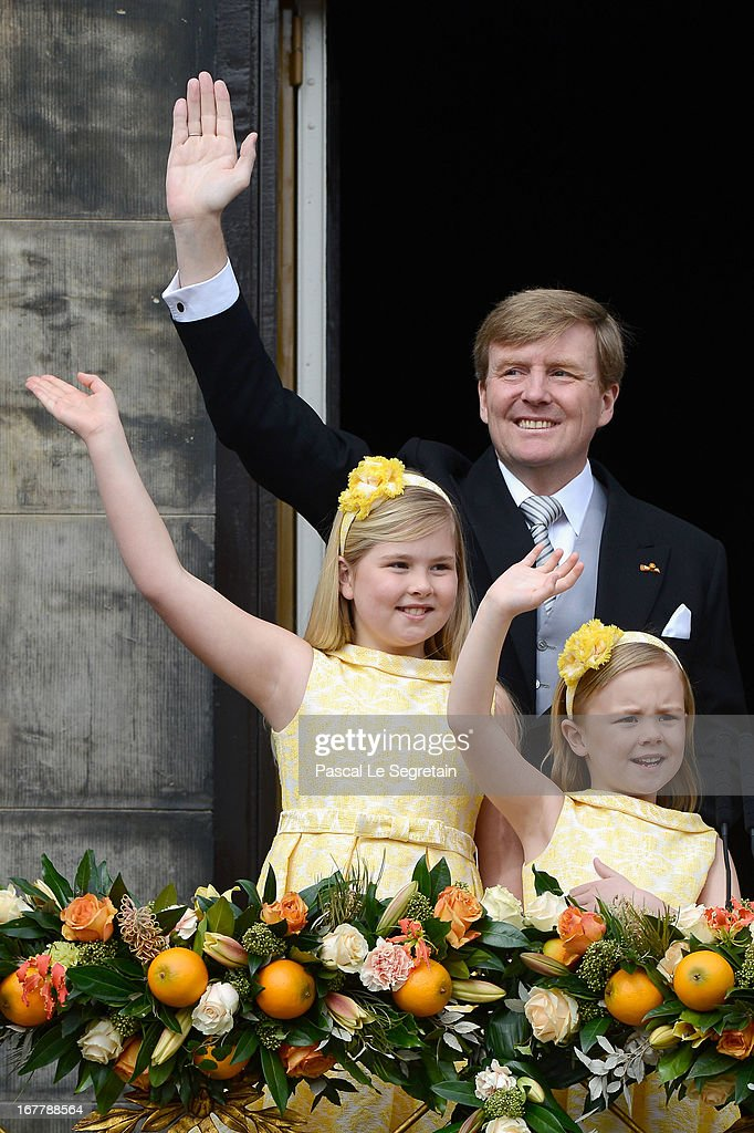 King Willem Alexander and his daughters Princess Catharina Amalia (L) and <a gi-track='captionPersonalityLinkClicked' href=/galleries/search?phrase=Princess+Ariane+of+the+Netherlands&family=editorial&specificpeople=4586156 ng-click='$event.stopPropagation()'>Princess Ariane of the Netherlands</a> (R) appear on the balcony of the Royal Palace to greet the public after the abdication of Queen Beatrix of The Netherlands and ahead of the Inauguration of King Willem Alexander of The Netherlands on April 30, 2013 in Amsterdam, Netherlands.