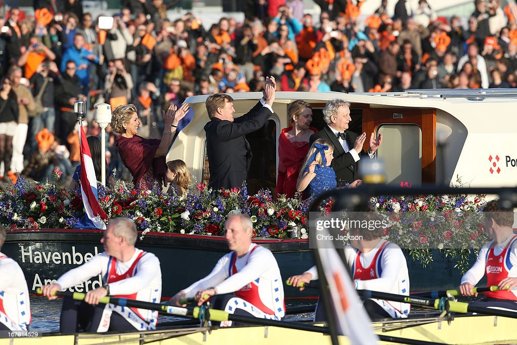 King Willem Alexander (C) and Queen Maxima (L) of The Netherlands are seen aboard the King's boat for the water pageant to celebrate the inauguration of King Willem Alexander of the Netherlands after the abdication of his mother Queen Beatrix of the Netherlands on April 30, 2013 in Amsterdam, Netherlands.