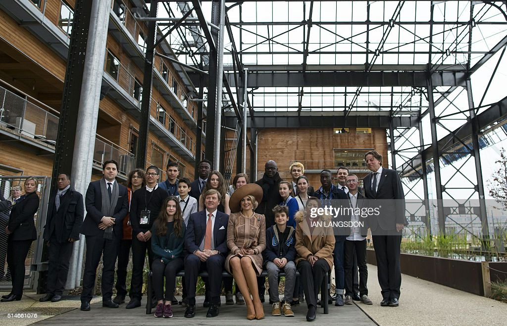 King Willem Alexander (2nd L, Front) and Queen Maxima of the Netherlands (C), sitting on a bench which they gifted to a youth association, pose alongside French Minister for Overseas Territories George Pau-Langevin (front R), former French footballer Lilian Thuram (Rear C) and youths during their visit the Halle Pajol youth hostel in Paris on March 10, 2016 at the start of their two-day state visit to France. / AFP / POOL / IAN