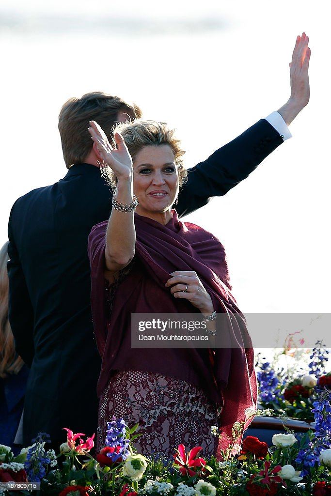 King Willem Alexander and Queen Maxima of the Netherlands wave to the crowd along the bank aboard the King's boat for the water pageant to celebrate the inauguration of King Willem of the Netherlands after the abdication of his mother Queen Beatrix of the Netherlands on April 30, 2013 in Amsterdam, Netherlands.