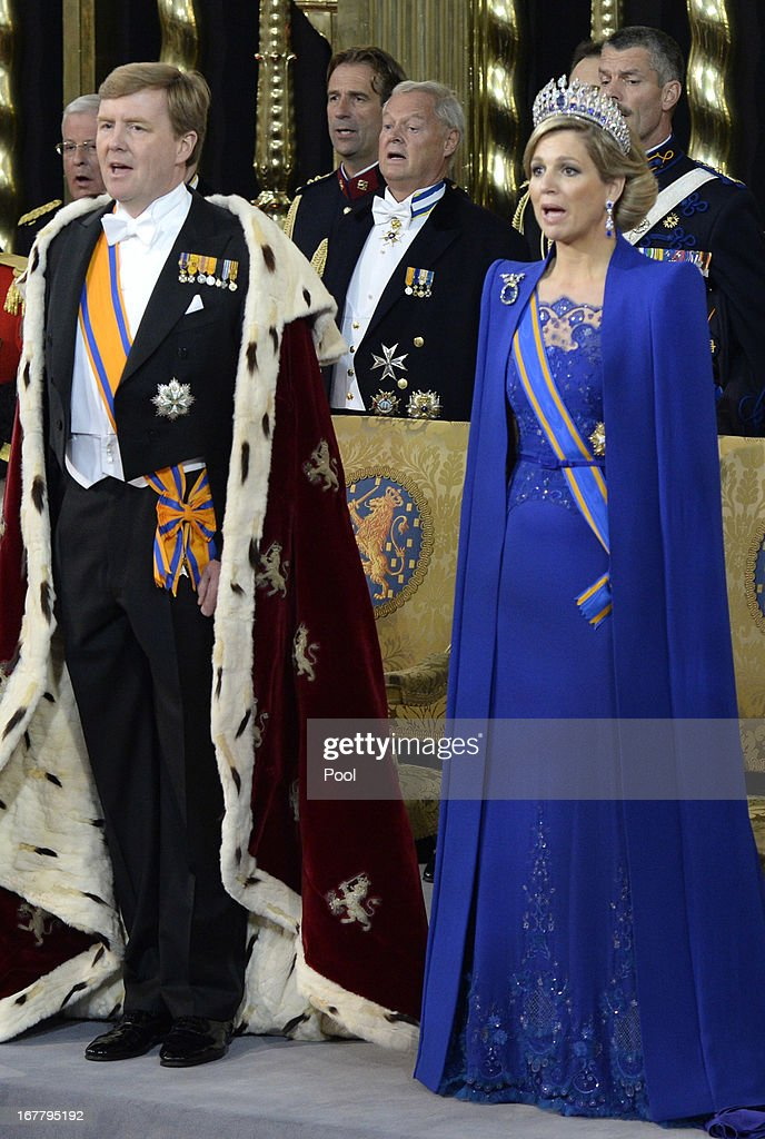 HM King Willem Alexander of the Netherlands and HM Queen Maxima of the Netherlands stand in front of their thrones near members of the royal household during their inauguration ceremony at New Church on April 30, 2013 in Amsterdam, Netherlands.