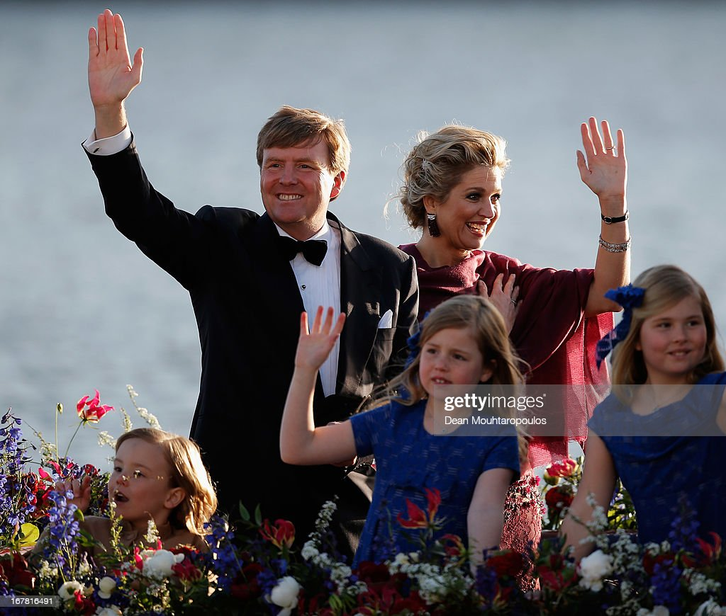 King Willem Alexander of the Netherlands, Queen Maxima of the Netherlands and their daughters Princess Catharina Amalia, Princess Ariane and Princess Alexia of the Netherlands wave to the crowd along the bank aboard the King's boat for the water pageant to celebrate the inauguration of King Willem of the Netherlands after the abdication of his mother Queen Beatrix of the Netherlands on April 30, 2013 in Amsterdam, Netherlands.