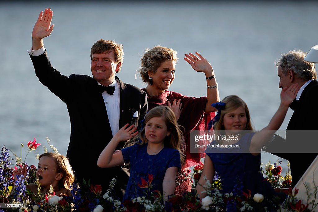 King Willem Alexander, Queen Maxima and their daughters Princess Catharina Amalia, Princess Ariane and Princess Alexia of the Netherlands wave to the crowd along the bank aboard the King's boat for the water pageant to celebrate the inauguration of King Willem of the Netherlands after the abdication of his mother Queen Beatrix of the Netherlands on April 30, 2013 in Amsterdam, Netherlands.