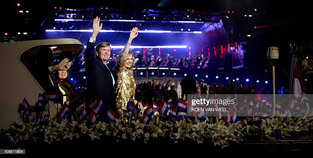 King Willem-Alexander (C) and Queen Maxima (R) wave while they leave on a boat after the Liberation Day celebration concert in Amsterdam on May 5, 2016. / AFP / ANP / Koen van Weel / Netherlands OUT
