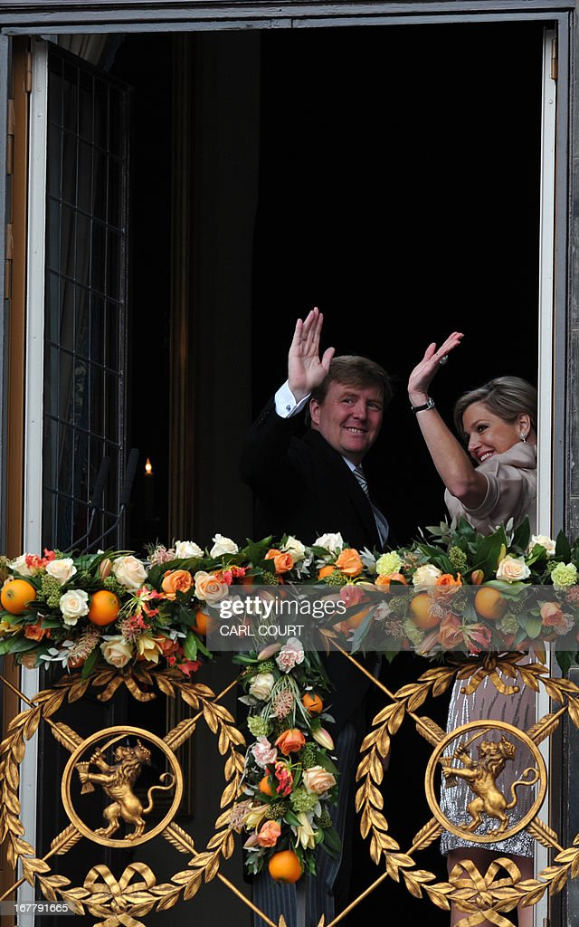 King Willem-Alexander of the Netherlands and his wife Queen Maxima wave to the crowd on April 30, 2013 gathered on Dam Square from the balcony of the Royal Palace in Amsterdam, following the official abdication of Queen Beatrix of the Netherlands.