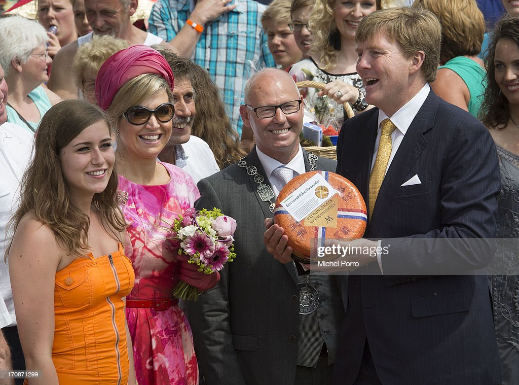 King Willem-Alexander of The Netherlands and Queen Maxima of The Netherlands receive a cheese during an official visit to the town centre on June 19, 2013 in 's-Heerenbroek, Netherlands.