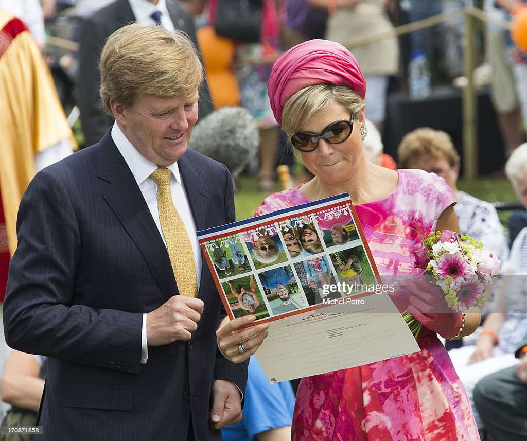 King Willem-Alexander of The Netherlands and Queen Maxima of The Netherlands receive a postcard during an official visit to the town centre on June 19, 2013 in 's-Heerenbroek, Netherlands.