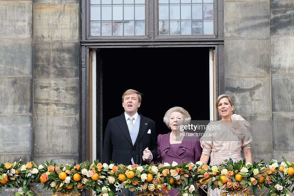 King Willem-Alexander of the Netherlands, his mother Princess Beatrix of the Netherlands (C) and wife Queen Maxima sing the national anthem as they greet the crowd on April 30, 2013 gathered on Dam Square from the balcony of the Royal Palace in Amsterdam, following the official abdication ceremony.