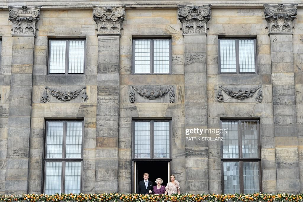King Willem-Alexander of the Netherlands, his mother Princess Beatrix of the Netherlands (C) and wife Queen Maxima greet the crowd on April 30, 2013 gathered on Dam Square from the balcony of the Royal Palace in Amsterdam, following the official abdication ceremony.