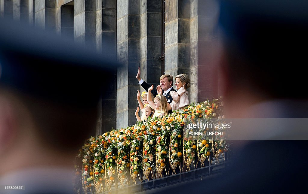 King Willem-Alexander of the Netherlands, his wife Queen Maxima (R) and their children Catharina-Amalia, Princess of Orange (front, L), Princess Ariane (front, R) and Princess Alexia (C) wave on April 30, 2013 to the crowd gathered on Dam Square from the balcony of the Royal Palace in Amsterdam, following the official abdication of Queen Beatrix of the Netherlands. AFP PHOTO / POOL / ROBIN UTRECHT