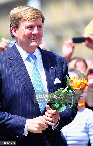 King WillemAlexander of The Netherlands holds two orange roses during a visit in BadenWuerttemberg on June 4 2013 in Stuttgart Germany