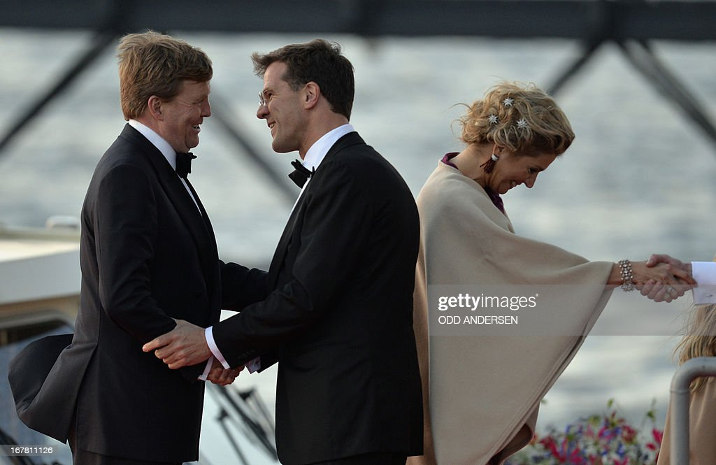 King Willem-Alexander of the Netherlands (L) shakes hands with Dutch Prime Minister Mark Rutte next to Queen Maxima of the Netherlands prior to step on a boat on April 30, 2013 prior to take part in a water pageant on the river IJ in Amsterdam on the day of his investiture
