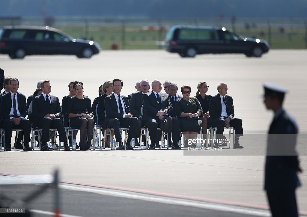 King Willem-Alexander (2L) sits with Queen Maxima (3L) and Prime Minister Mark Rutte (4L) as unidentified bodies from the crash of Malaysia Airlines flight MH17 are transferred to hearses on July 23, 2014 in Eindhoven, Netherlands. Today the people of the Netherlands are holding a national day of mourning. Malaysian Airlines flight MH17 was travelling from Amsterdam to Kuala Lumpur when it crashed in eastern Ukraine killing all 298 passengers. The aircraft was allegedly shot down by a missile and investigations continue to find the perpetrators of the attack.
