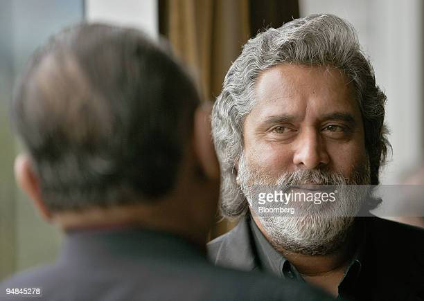 Kingfisher Airlines Ltd Chairman Vijay Mallya speaks to a colleague on the sidelines of the International Air Transport Association /Asian Aerospace...