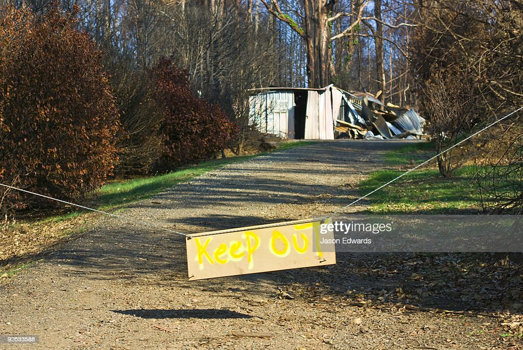 A sign posted outside a house destroyed by fire warns not to enter.