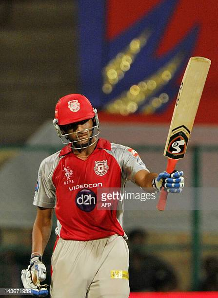 Kings XI Punjab batsman Nitin Saini raises his bat after scoring a half century during the IPL Twenty20 cricket match between Royal Challenger...