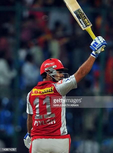 Kings XI Punjab batsman Piyush Chawla raises his bat after hitting the winning shot against Royal Challengers Bangalore during the IPL Twenty20...