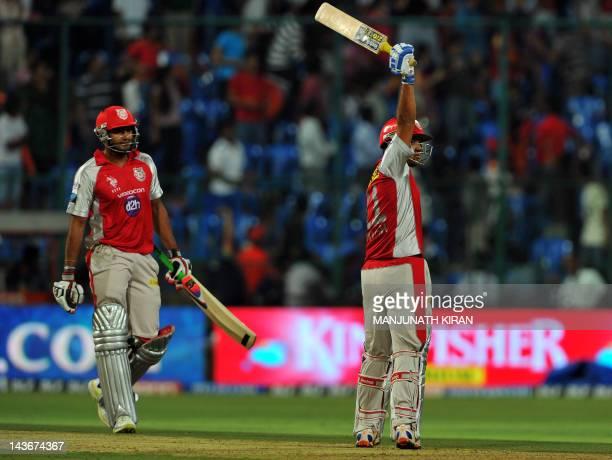 Kings XI Punjab batsman Piyush Chawla raises his bat after hitting the winning shot against Royal Challengers Bangalore while team mate Paras Dogra...
