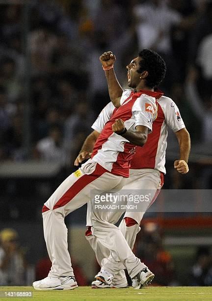 Kings XI Punjab bowler Parvinder Awana celebrates taking the wicket of Royal Challengers Bangalore batsman Saurabh Tiwary with a teammate during the...