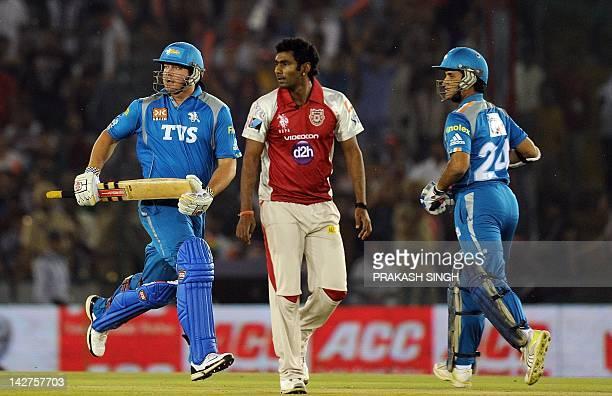 Kings XI Punjab bowler Parvinder Awana watches as Pune Warriors batsman Jesse Ryder and Saurav Gangulay run between the wickets during the IPL...