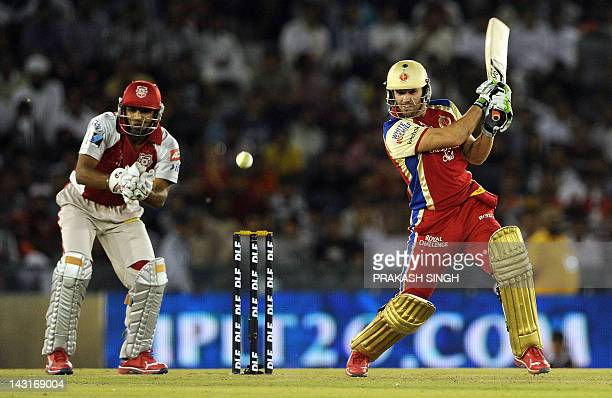 Kings XI Punjab wicket keeper Nitin Saini looks on as Royal Challengers Bangalore batsman AB de Villiers plays a shot during the IPL Twenty20 cricket...
