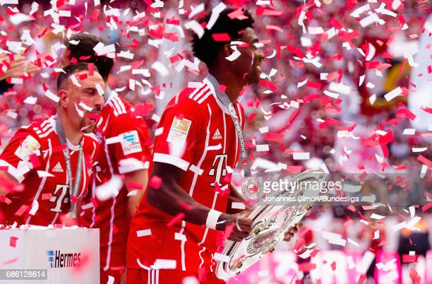 Kingsley Coman of Bayern lifts the championship trophy during an awarding ceremony in celebration of the 67th German Championship title following the...