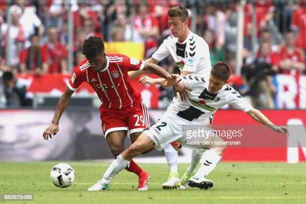 Kingsley Coman of Bayern Muenchen battles for the ball with Aleksandar Ignjovski of Freiburg during the Bundesliga match between Bayern Muenchen and...