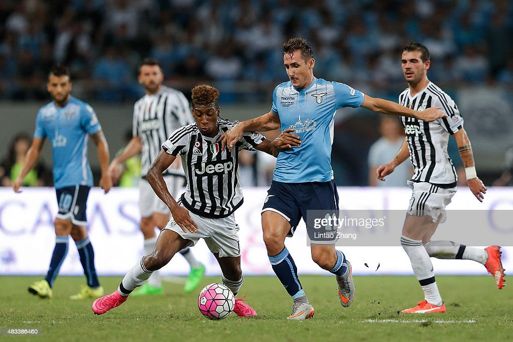 Kingsley Coman (L) of Juventus FC contests the ball against Miroslav Klose (R) of Lazio during the Italian Super Cup final football match between Juventus and Lazio at Shanghai Stadium on August 8, 2015 in Shanghai, China.