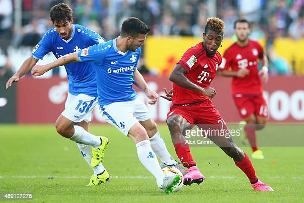 Kingsley Coman of Muenchen is challenged by Jerome Gondorf and Gyorgy Garics of Darmstadt during the Bundesliga match between SV Darmstadt 98 and FC...