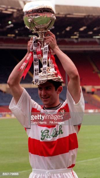 Kingstonian's goal scorer Tarkan Mustafa holds aloft the Umbro FA Trophy after Kingstonian defeated Forest Green Rovers 10 in the final at Wembley...