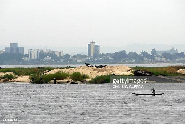 Kinshasa Democratic Republic of the Congo A Congolese fisherman passes 24 July 2006 with his canoe in front of the Brazzaville skyline in the harbour...