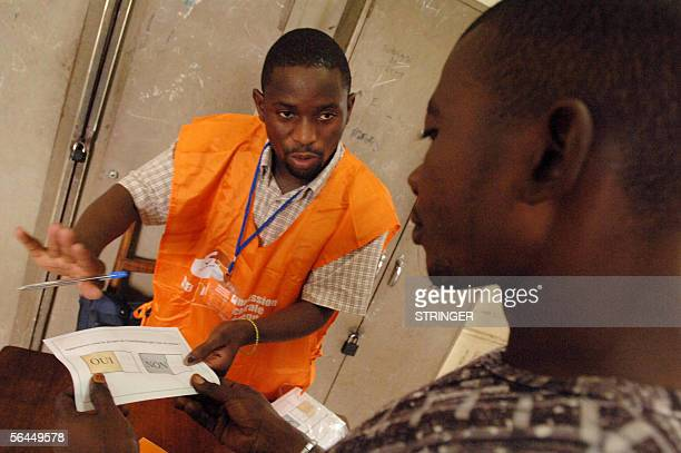Kinshasa Democratic Republic of the Congo An election official explains the voting process to a voter at a polling station in the district of Matonge...