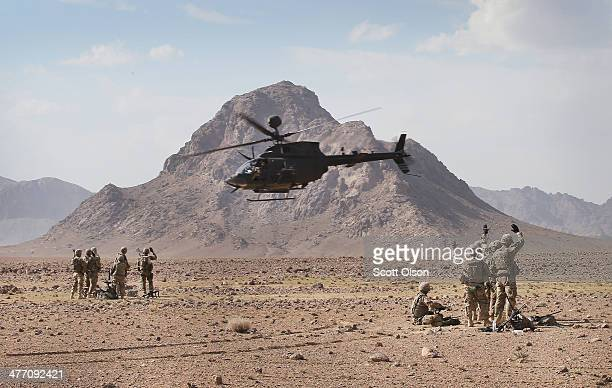 Kiowa Warrior helicopter flies above soldiers with 4th Squadron 2d Cavalry Regiment during a livefire exercise in the desert on March 6 2014 near...