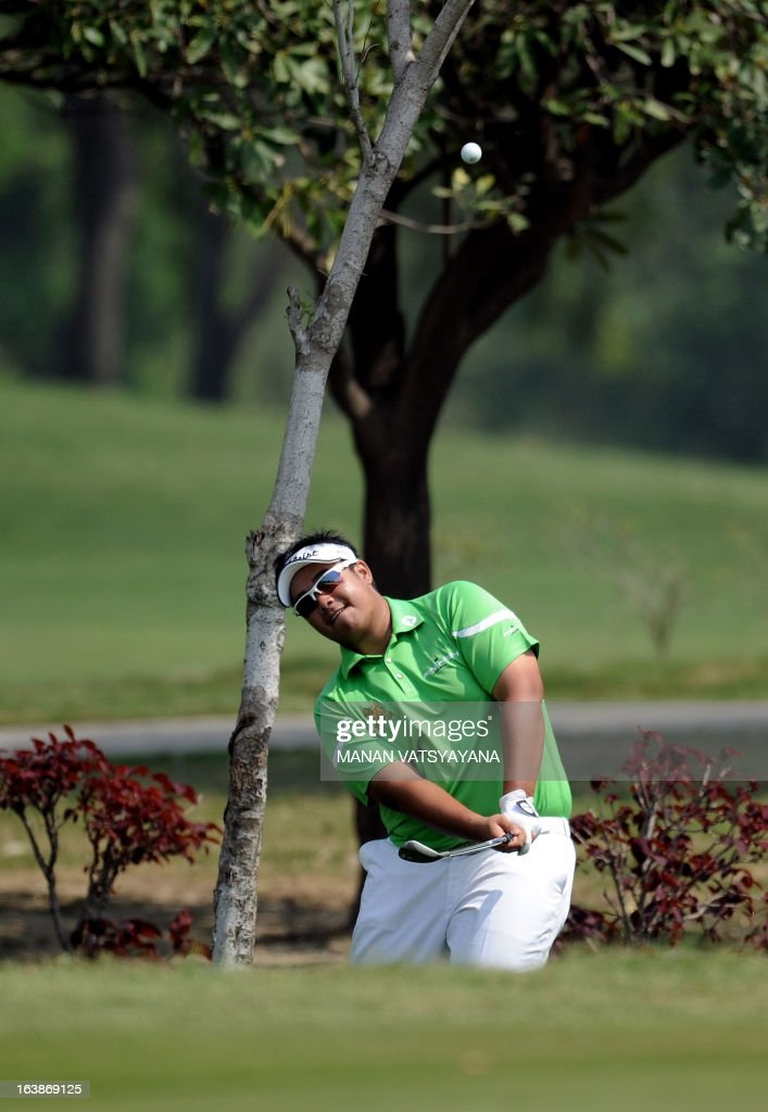 Kiradech Aphibarnrat of Thailand hits the ball out of bushes on the fourth green during the final day of the Avantha Masters golf tournament in Greater Noida, on the outskirts of New Delhi on March 17, 2013.