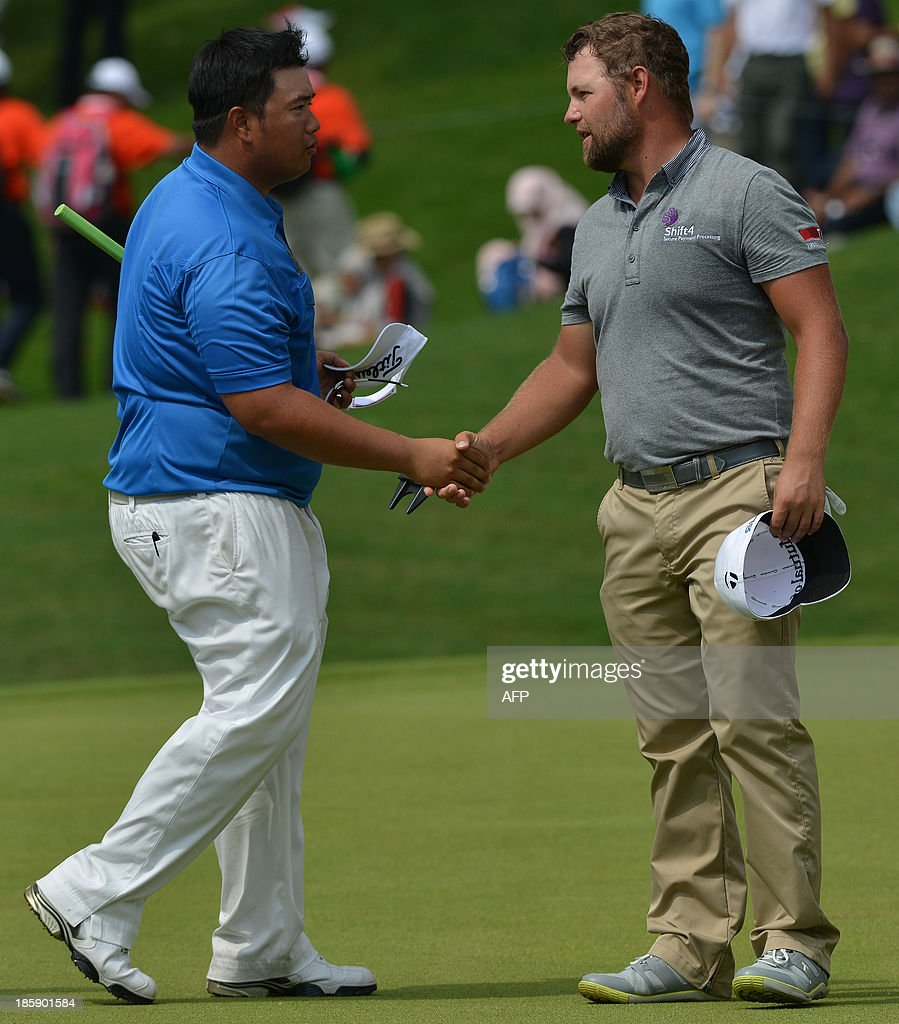 Kiradech Aphibarnrat of Thailand (L) shakes hands with Ryan Moore of the US (R) after finishing the last putt on the 18th hole during the third round of the CIMB Asia Pacific Classic golf tournament at the Kuala Lumpur Golf and Country Club (KLGCC) on October 26, 2013. AFP PHOTO / MOHD RASFAN