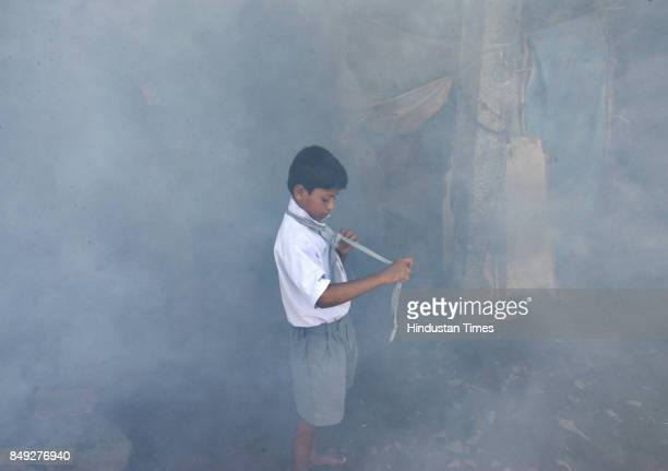 Kiran Nirmal a resident of the Shyamnagar slums at Bhandup gets ready to attend school as the BMC officials start fogging the area to prevent...