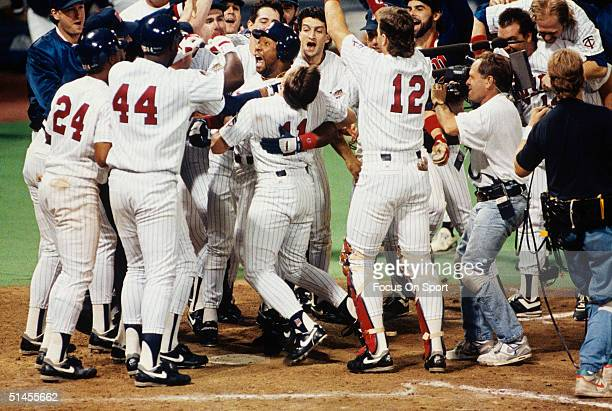 Kirby Puckett of the Minnesota Twins is mobbed by his teammates at home plate after hitting the game winning home run against the Atlanta Braves in...