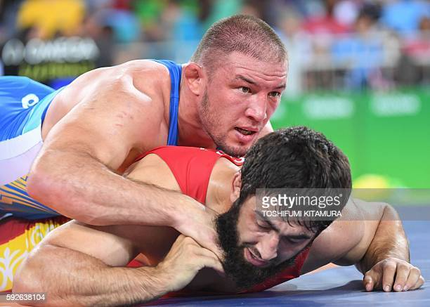 Kirghyzstan's Magomed Musaev wrestles with Ukraine's Valerii Andriitsev in their men's 97kg freestyle quarterfinal match on August 21 during the...
