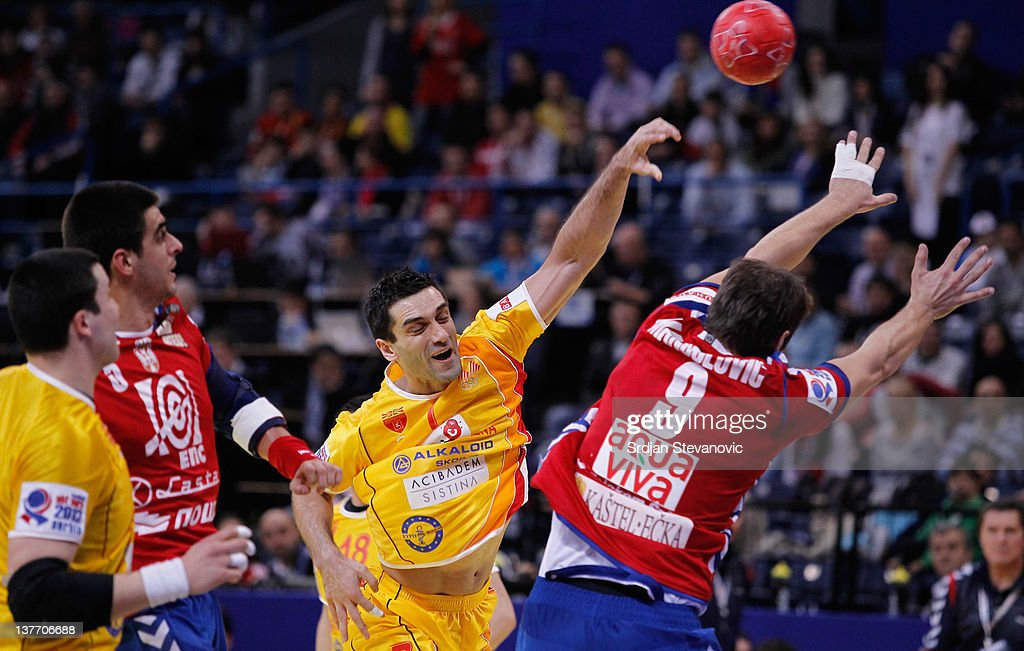 Kiril Lazarov (C) of Macedonia shoots the ball past Nikola Manojlovic (R) and Zarko Sesum (L) of Serbia during the Men's European Handball Championship 2012 second round group one match between Serbia and Macedonia at Arena Hall on January 25, 2012 in Belgrade, Serbia.