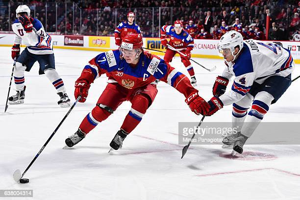 Kirill Kaprizov of Team Russia protects the puck from Caleb Jones of Team United States during the 2017 IIHF World Junior Championship semifinal game...