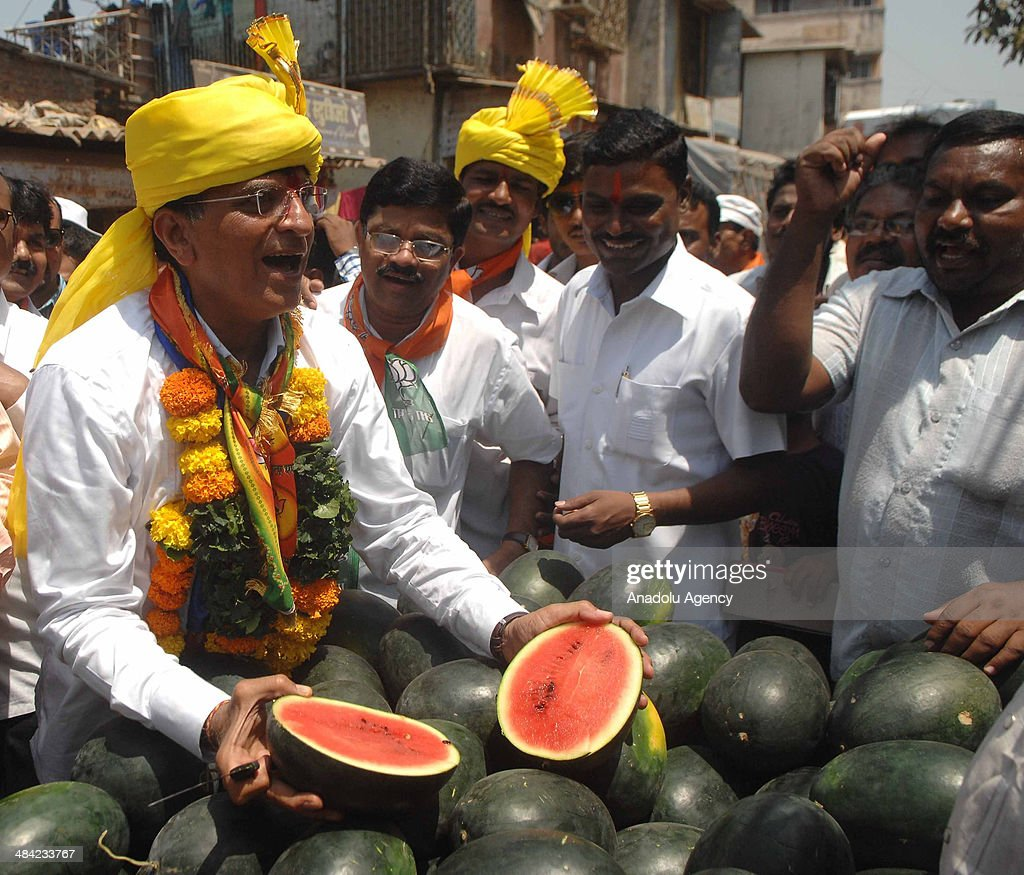 Kirit Somaiya, leader of Bharatiya Janata Party and contestant from Mumbai's northeast constituency campaigns in Mankhurd, an eastern Mumbai suburb, gives water melon to the crowd on April 11, 2014 in Mumbai, India.