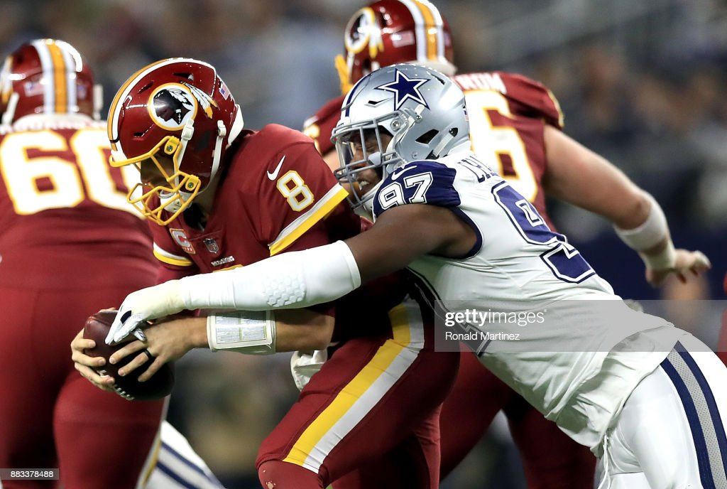 Kirk Cousins #8 of the Washington Redskins is sacked by Taco Charlton #97 of the Dallas Cowboys in the second quarter at AT&T Stadium on November 30, 2017 in Arlington, Texas.