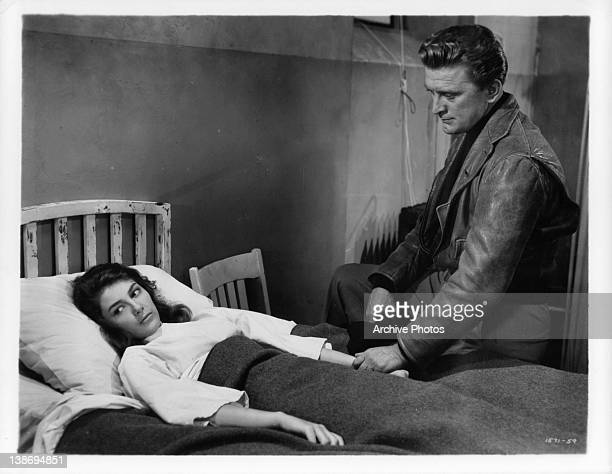 Kirk Douglas looking down at woman in bed in a scene from the film 'The Story Of Three Loves' 1953