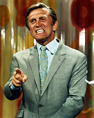 Kirk Douglas US actor wearing a grey jacket a light blue shirt and a paisley pattern tie angily pointing his finger with a grimace on his face circa...