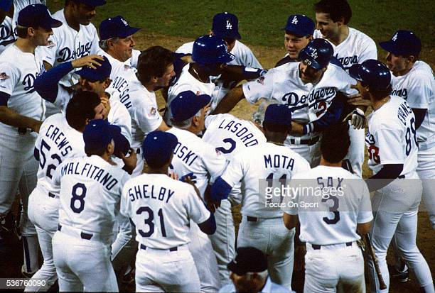 Kirk Gibson of the Los Angeles Dodgers celebrates with teammates after he hit a game winning pitchhit solo home run in the bottom of the ninth inning...